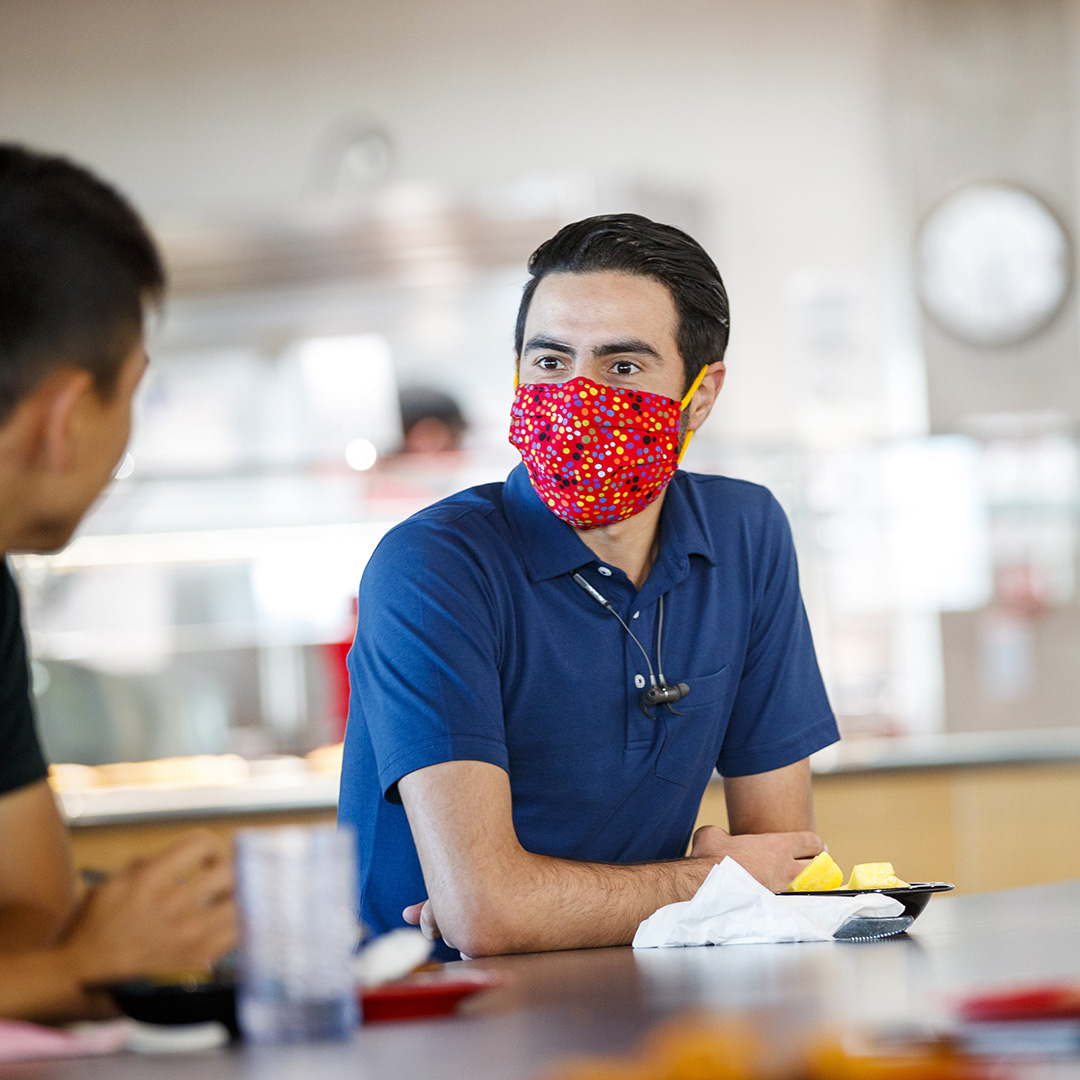 Students talking with masks on at the table in the Cather Dining Center