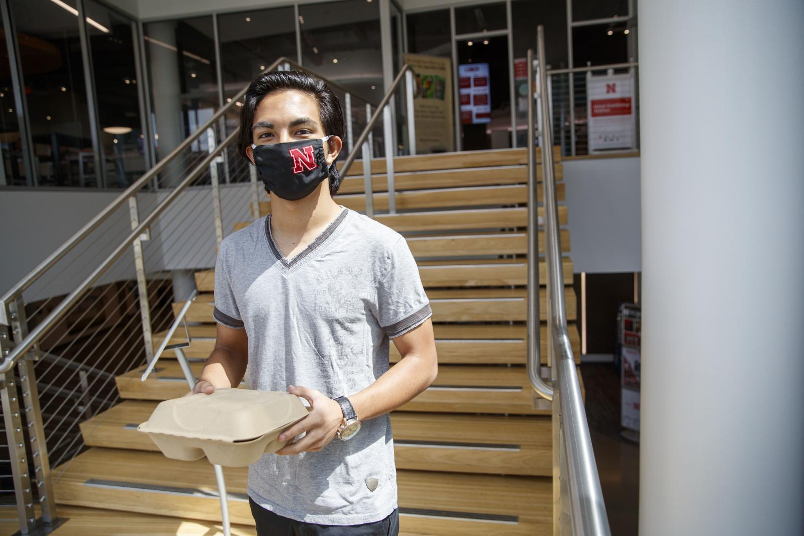 Student leaves dining center with to-go container