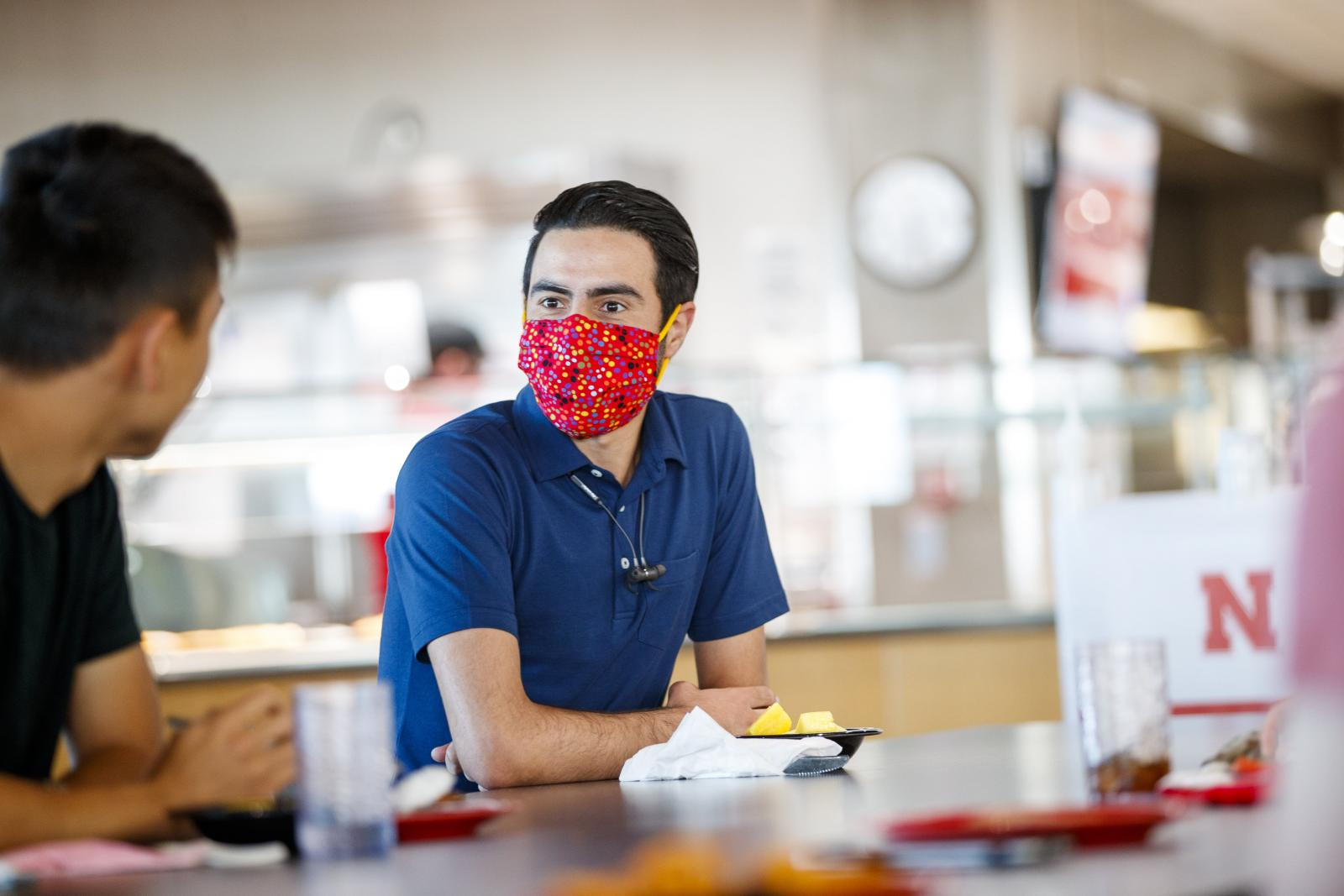 Student sitting at a table in the dining center with a mask on.